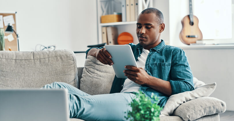 Man relaxing on couch looking at tablet