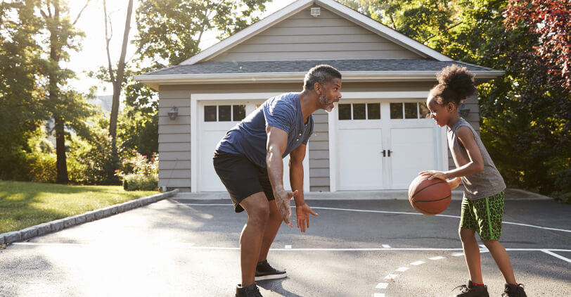 A dad and his daughter playing basketball in the driveway