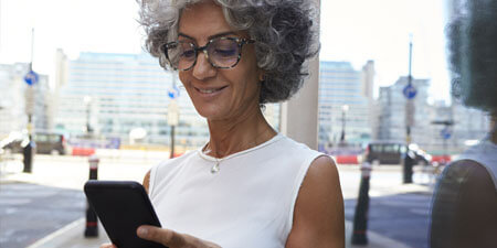 A woman looking at the screen of her smartphone.