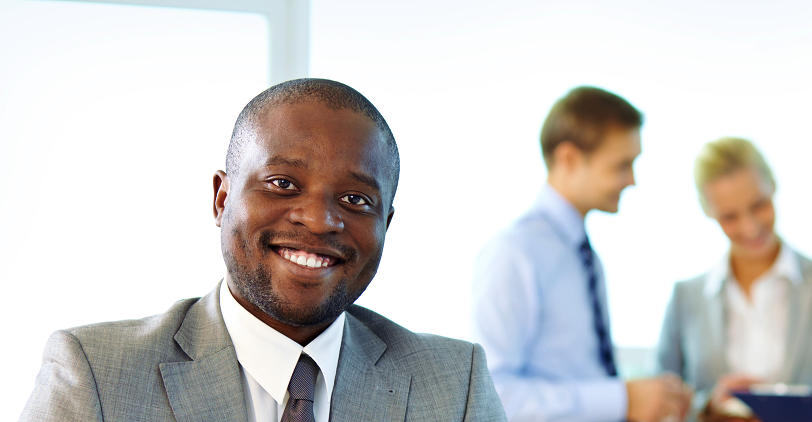 African heritage businessman smiling in front of team
