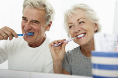 Husband and wife brushing teeth together