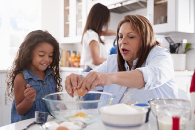 Mother and daughter cracking eggs in kitchen