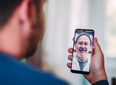 A man attending a virtual doctor's visit on a smartphone.