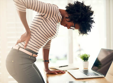A woman standing at her desk with back pain