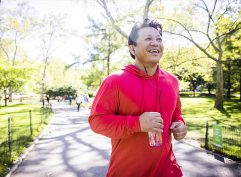 A happy man jogging in a park