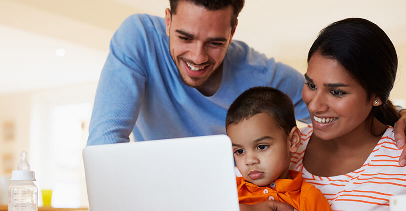 Family looking at laptop in house banner