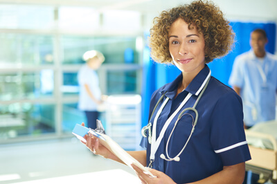 Female medical professional smiling and holding clip board