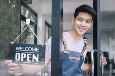 business owner of coffee shop with we are open sign on door