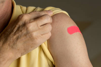Individual displaying a pink adhesive bandage on their upper arm
