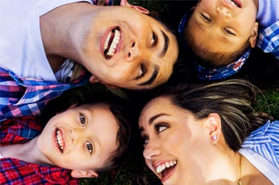 Happy family lying on the ground outside