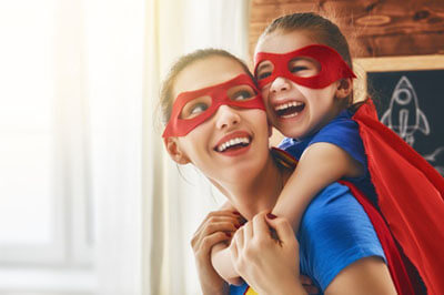 Happy mom and kid dressed as super heroes