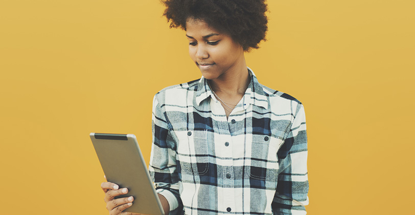 Girl holding an iPad against a yellow background