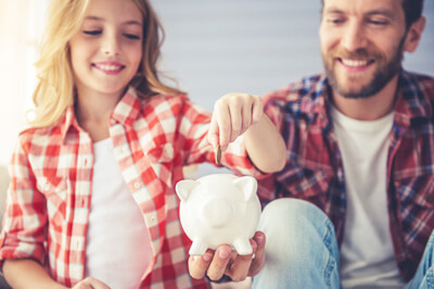 Parent and child saving money in a piggybank