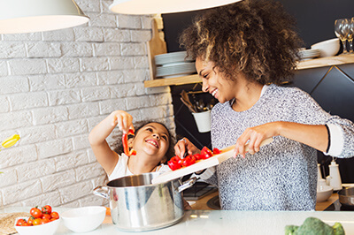 Mother and daughter preparing food together