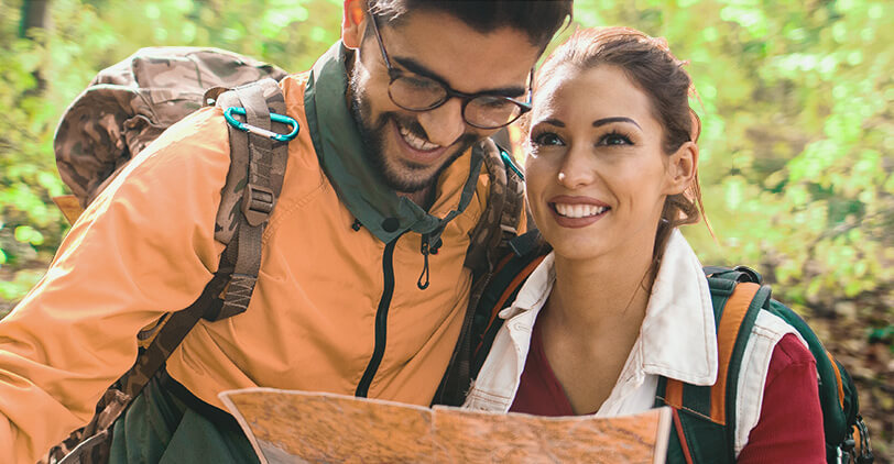 couple hiking together while looking at map of trail