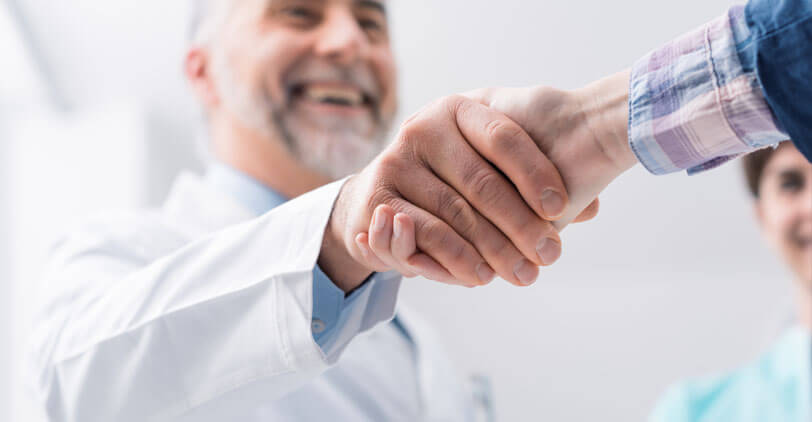 Trusted doctor shaking hands with a patient