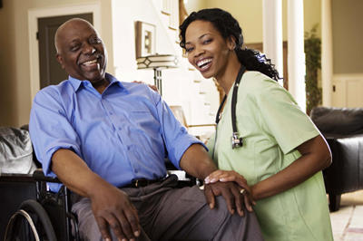 Man in wheelchair laughing with caregiver