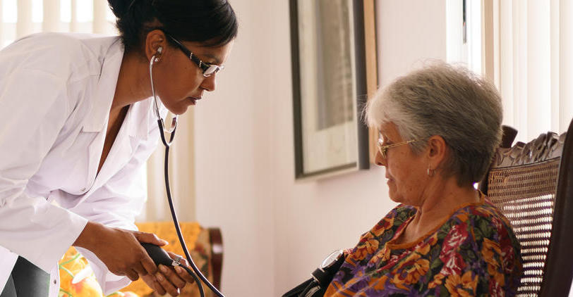 Doctor checking blood pressure of patient in care home