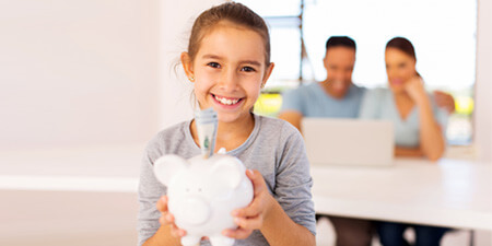 Happy child with a piggybank enjoying a morning with her parents