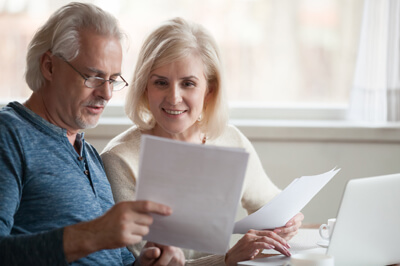 Elder couple reading about savings
