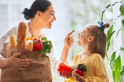 Mom and daughter happily unloading healthy groceries