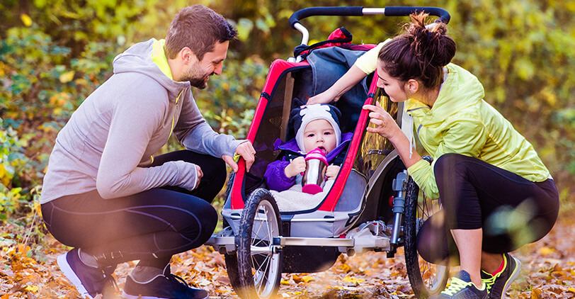 Parents in exercise outfits with child in an all-terrain buggy